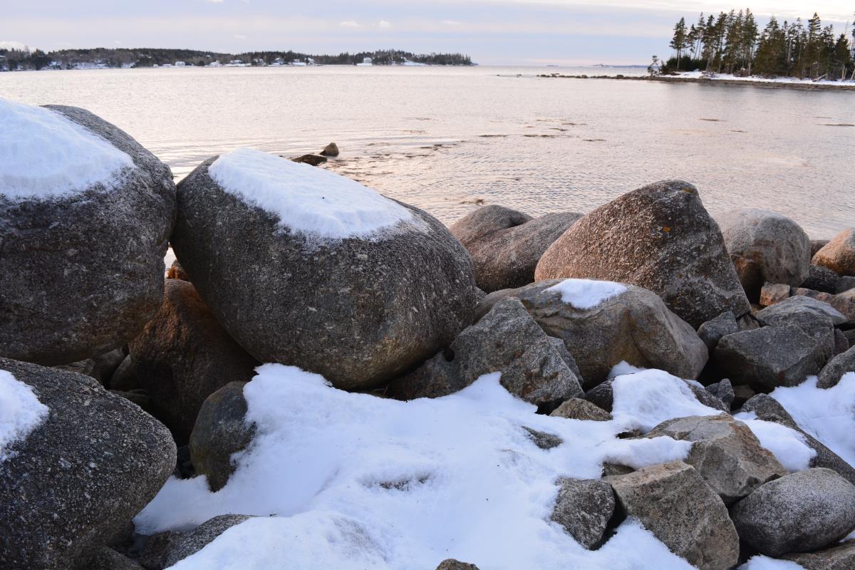 snowy rocks at the edge of lake