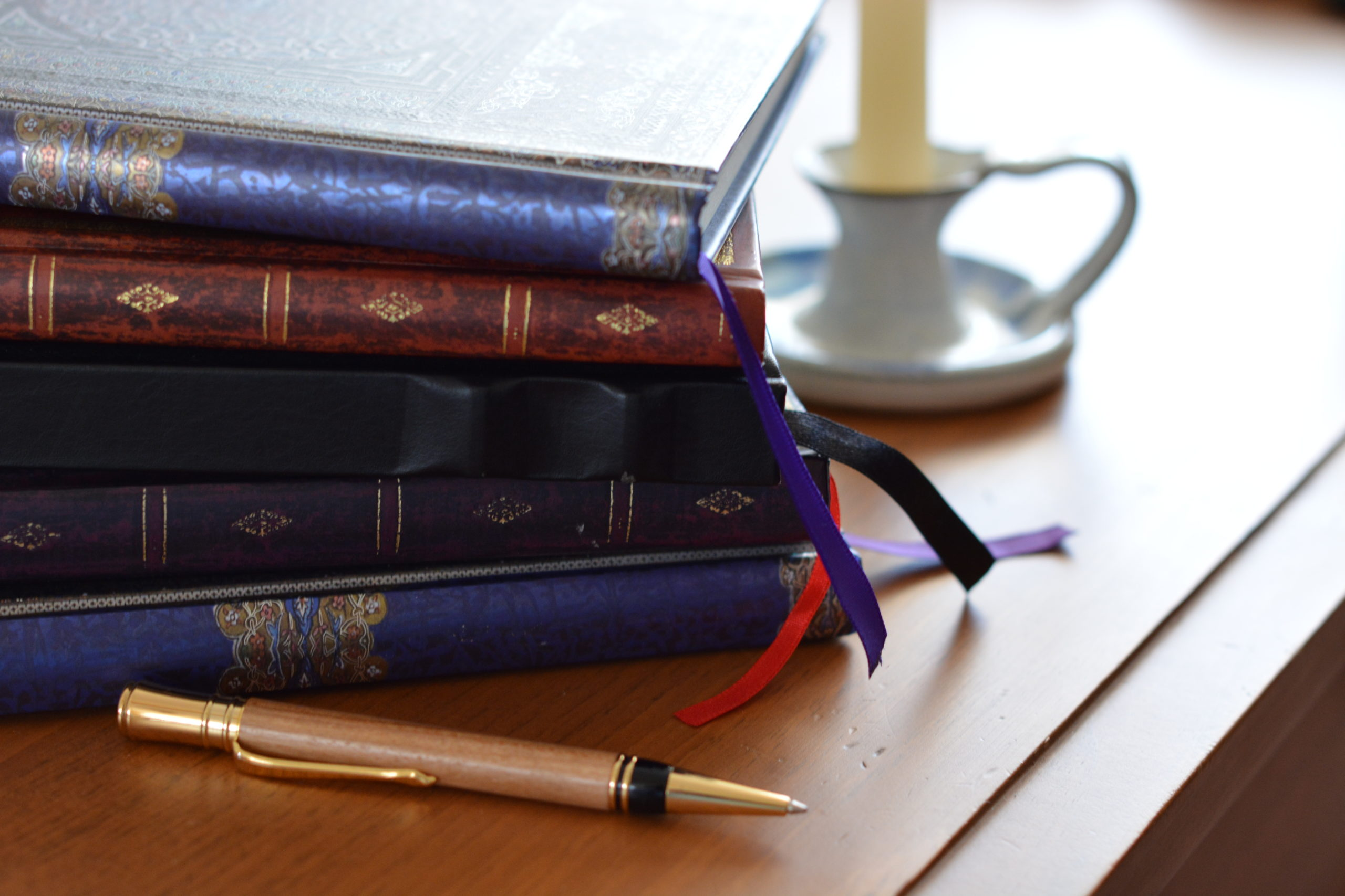 stack of journals and a pen